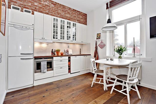Một mảng tường gạch của không gian cũ vẫn được lưu giữ, tạo điểm nhấn ấm áp cho góc bếp.