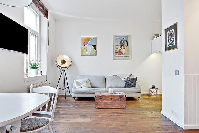 Góc tiếp khách đơn giản mà tinh tế, với chiếc vali cũ được tái chế thành bàn và sofa mang màu ghi xám nhẹ nhàng.