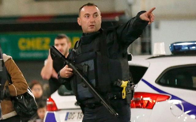Một cảnh sát hướng dẫn cho người dân ở cạnh hiện trường vụ đấu súng sơ tán. (Ảnh: Reuters).