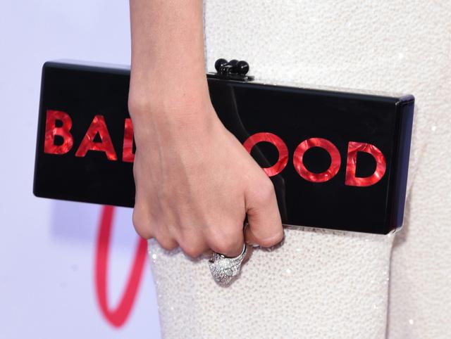 Phụ kiện đi kèm của cô là chiếc clutch màu đen với dòng chữ Bad Blood nổi bật.