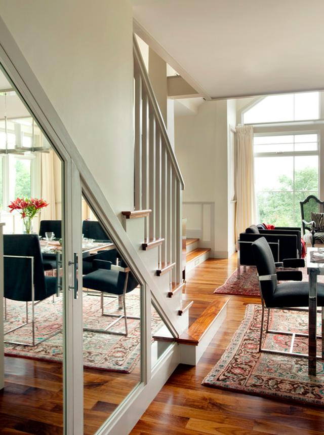 Gầm cầu thang còn có thể được sử dụng làm tủ mặt kính hay làm gương soi, giúp bạn có cảm giác không gian trong phòng được mở rộng hơn.