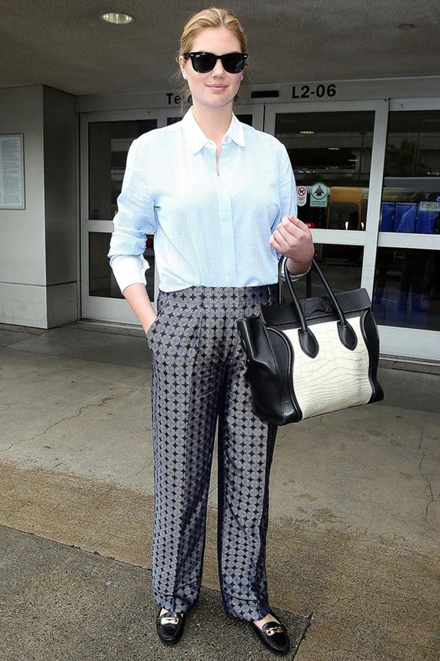 """Áo sơ mi với quần âu ống rộng không làm diện mạo của Kate Upton trở nên """"quê mùa"""" chút nào, trái lại còn khiến nữ diễn viên – người mẫu nóng bỏng này trở nên cá tính khác lạ."""