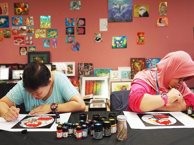 Sun Yimei và Siti Farhana Bte Borhan, 29 tuổi, vẽ những bức hình acrylic của Nila với phong cách của riêng họ. Ảnh: SINGSOC