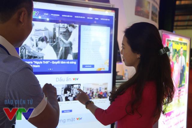 Kỹ thuật viên của VTV News giới thiệu cho khách tham quan các sản phẩm của báo