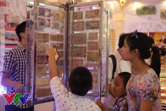 Các em nhỏ rất hứng thứ với các đồng tiền ngoại tệ tại gian hàng của Ngân hàng nhà nước