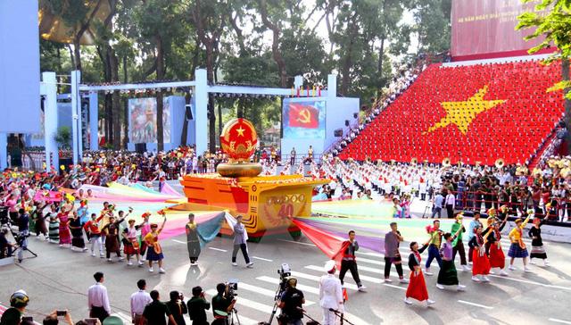 Đi đầu là Quốc huy nước Cộng hòa Xã hội Chủ nghĩa Việt Nam trên nền trống đồng, biểu hiện ý chí khát vọng của dân tộc Việt Nam. (Ảnh: TTXVN)