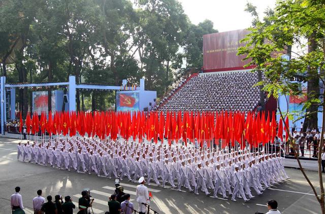 Khối cờ Đảng, cờ Tổ quốc do 200 thanh niên nghiêm trang rước qua lễ đài, tượng trưng cho lý tưởng, chiến thắng, bản lĩnh, trí tuệ lãnh đạo của Đảng và khí phách của khối đại đoàn kết toàn dân tộc. (Ảnh: TTXVN)