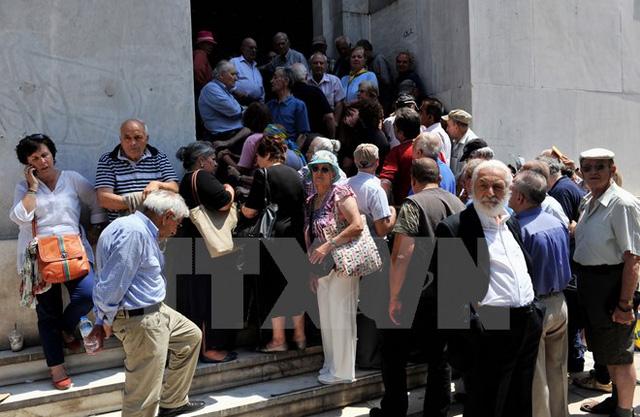 Người dân xếp hàng chờ rút tiền bên ngoài chi nhánh Ngân hàng quốc gia Hy Lạp đã đóng cửa ở Thessaloniki ngày 29/6. (Ảnh: AFP/TTXVN)