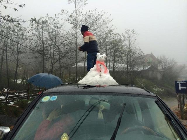 Có bạn trẻ còn thích thú làm người tuyết trên nóc xe (ảnh: Dân Trí)