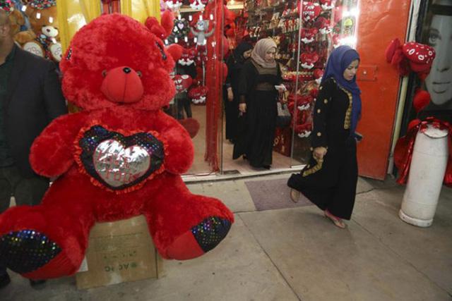 Một người phụ nữ rời khỏi cửa hàng bán đồ lưu niệm ở Baghdad (Iraq) (ảnh: AP)