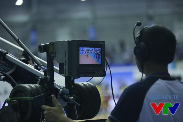 Một quay phim đang điều khiển máy cẩu để giúp khán giả có cái nhìn toàn cảnh sân đấu bóng chuyền từ trên cao.