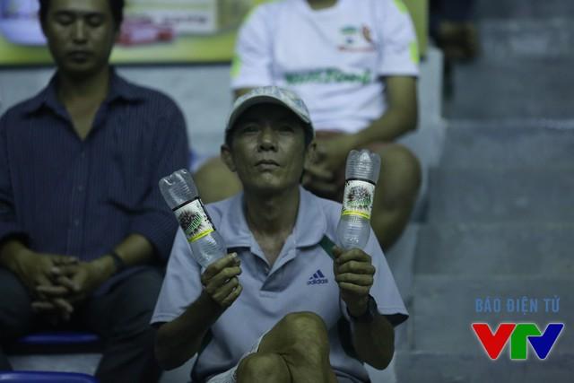 Một CĐV trung niên cuồng nhiệt dùng chai nước cổ vũ các VĐV dưới sân.