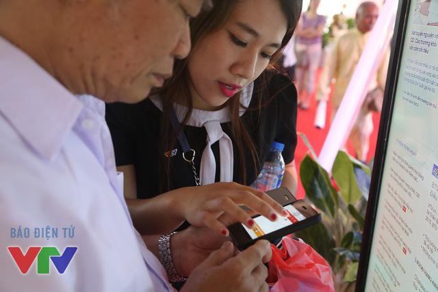 Kỹ thuật viên của Báo điện tử VTV News hướng dẫn độc giả cài ứng dụng Báo VTV trên mobile