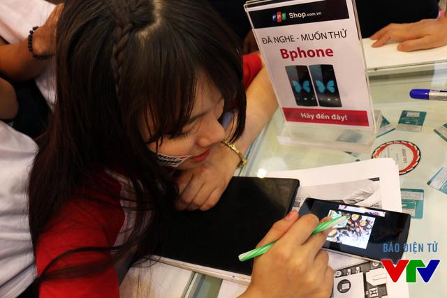 Vân Anh - một nữ sinh Bách Khoa cùng nhân viên của Bkav dùng bút bi để thử độ bền màn hình BPhone