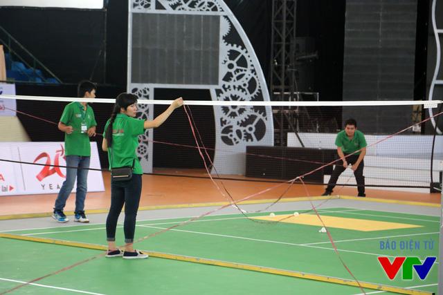 Các tình nguyện viên sử dụng dây để niêm phong sân thi đấu sau khi các đội tuyển hoàn thành việc thử sân