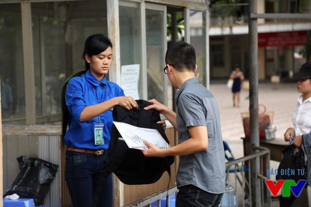 Các tình nguyện viên giúp đỡ thí sinh bảo quản đồ đạc trong khi thi