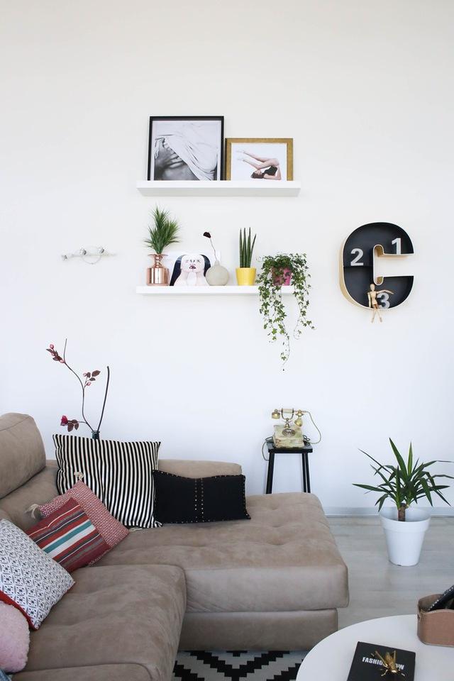 Những chậu cây nhỏ và đồ trang trí giúp mảng tường trắng thêm phần nổi bật.