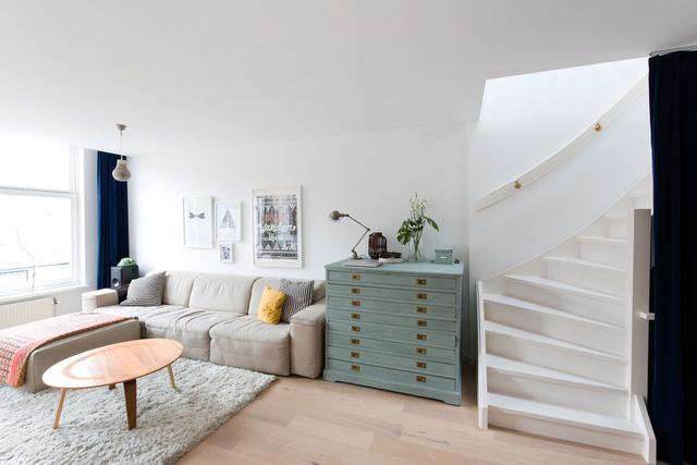 Cầu thang được thiết kế với tông màu sáng, nằm gọn gàng bên cạnh không gian tiếp khách, đọc sách.