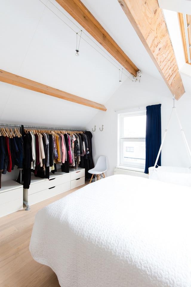 Chủ nhân sử dụng những mắc treo dọc theo bề ngang căn phòng để làm nơi cất giữ quần áo.