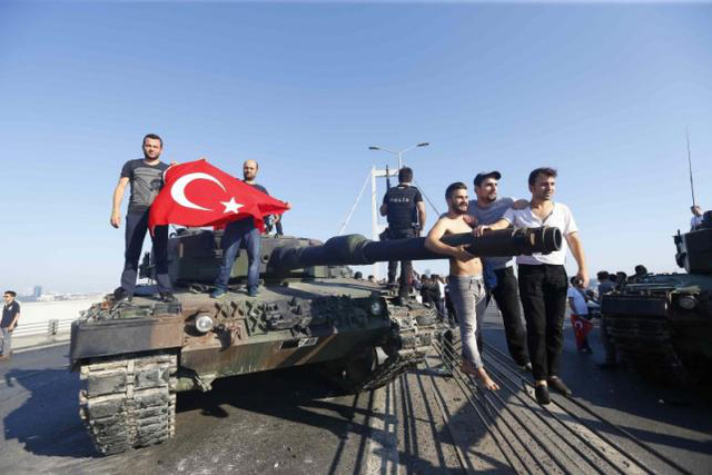 Người dân giương quốc kỳ đứng trên xe tăng của quân đội Thổ Nhĩ Kỳ.