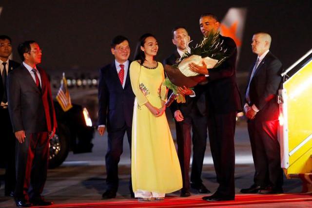 Tổng thống Obama nhận hoa từ đoàn tiếp đón tại sân bay Nội Bài (Ảnh: Reuters)