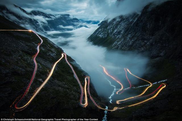 Ngày 27/5, danh tính nhiếp ảnh gia và bức ảnh chiến thắng cuộc thi ảnh du lịch thường niên của National Geographic mới được công bố, nhưng ngay từ lúc này, những bức ảnh đẹp nhất đã được hé lộ. Trong hình, nhiếp ảnh gia Christoph Schaarschmidt chụp con đường quanh co với ánh đèn xe cộ biến mất trong màn sương mù ở Trollstigen, Na Uy.