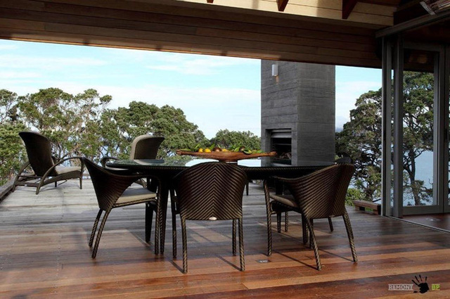 Phòng khách kiêm phòng ăn tối giản với một bộ bàn ghế, nhìn thẳng ra mái hiên.
