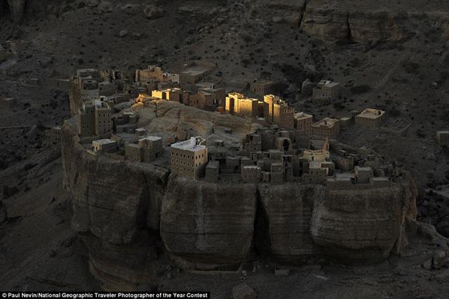 Tác giả Paul Nevin chụp bức ảnh này của ngôi làng giống như pháo đài, nằm trên vách đá khổng lồ ở Wadi Dohan, Yemen, lúc mặt trời mọc.