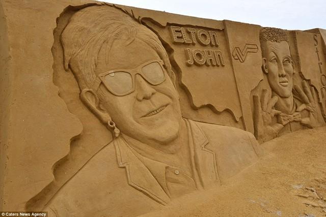 Hình ảnh Elton John mỉm cười trên cát. Chân dung của ông ông được khắc cùng với các ca sĩ khác như Marvin Gaye, Prince, John Lennon và Tina Turner