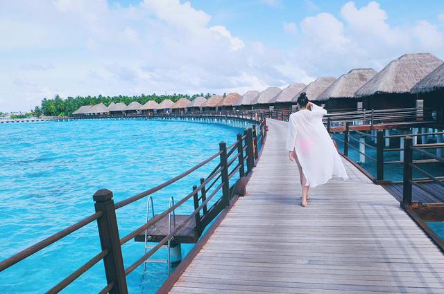 Cô kết hợp chiếc áo choàng dài màu trắng với bộ bikini nóng bỏng