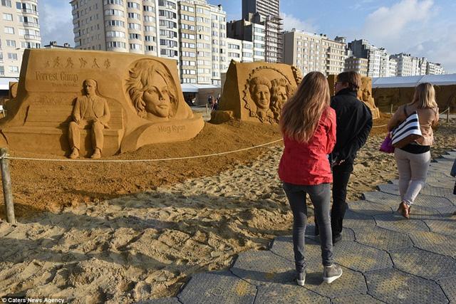 Du khách tham quan các tác phẩm điêu khắc trên cát.