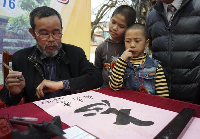 Các em nhỏ đang chờ đợi được lấy chữ Chí vừa được viết xong.