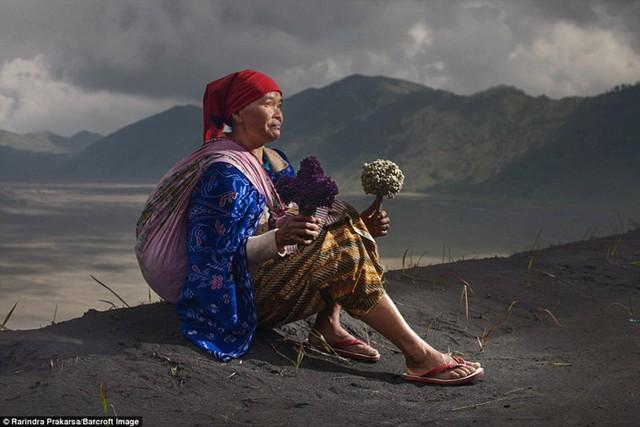 Người phụ nữ ngồi bệt trên những đám tro, tay cầm 2 bó hoa.