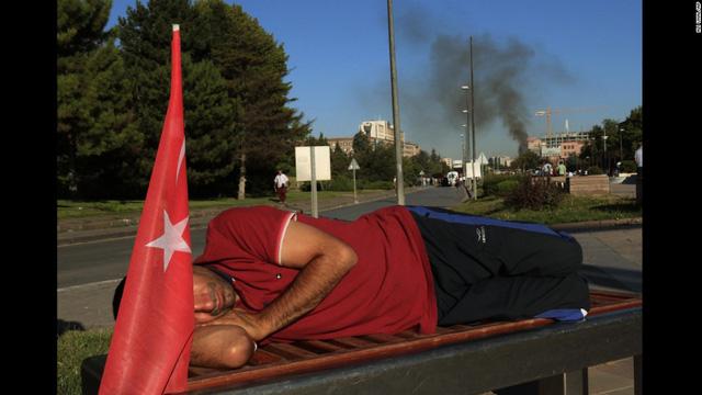 Một người dân mệt mỏi nằm dài trên băng ghế sau khi cuộc đảo chính kết thúc.