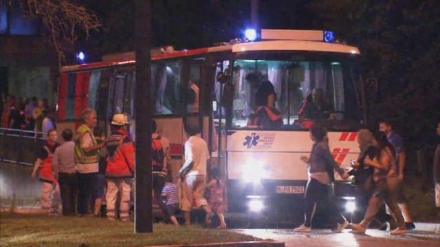 Người dân lên xe bus đi sơ tán sau khi vụ xả súng xảy ra.