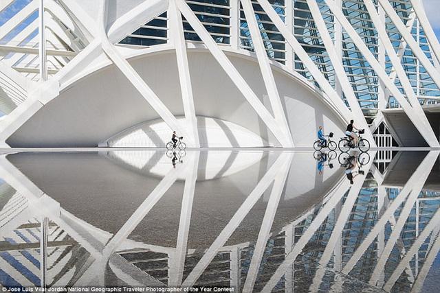 Hình ảnh người đi xe đạp phản chiếu trên mặt nước trong không gian thành phố nghệ thuật và khoa học tuyệt đẹp thuộc Valencia, Tây Ban Nha.