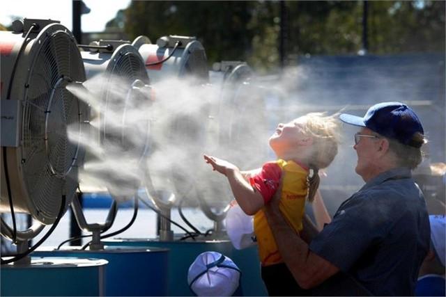 Một CĐV nhí của Australia Open tránh nóng trước quạt làm mát loại lớn