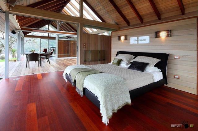 Giường màu đen, sàn gỗ nâu đỏ, thêm vào đó là đèn trang trí khiến phòng ngủ ấm áp hơn.