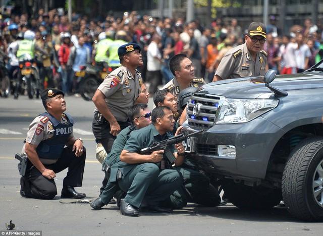 Cảnh sát ẩn náu sau chiếc ô tô trong lúc truy tìm kẻ gây ra vụ khủng bố