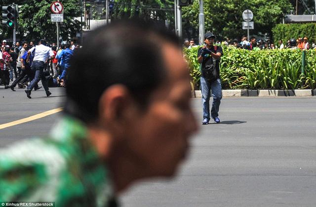 Một người dân vội vã chạy qua ống kính máy ảnh sau khi nhìn thấy tên khủng bố