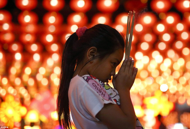 Bé gái cầu nguyện tại đền Siam Tai Tien Kong ở Thái Lan (Ảnh: EPA)