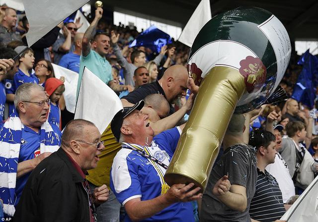 Chai sâm panh khổng lồ đã được các CĐV mang đến để chung vui với thầy trò HLV Ranieri. Leicester City xứng đáng nhận được mọi lời chúc mừng trong ngày mà câu chuyện cổ tích của họ đã tìm được cái kết có hậu