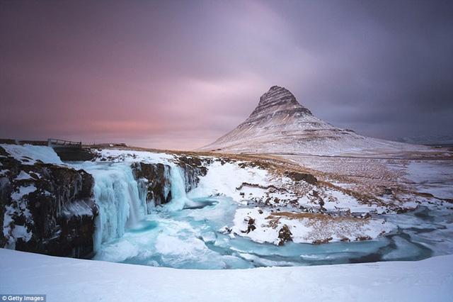 Ở Iceland, hiện tượng mặt trời lúc nửa đêm cũng xảy ra tương tự với Na Uy. Trong hình là hoàng hôn khuất sau dãy núi Kirkjufell tại bán đảo Snæfellsnes.