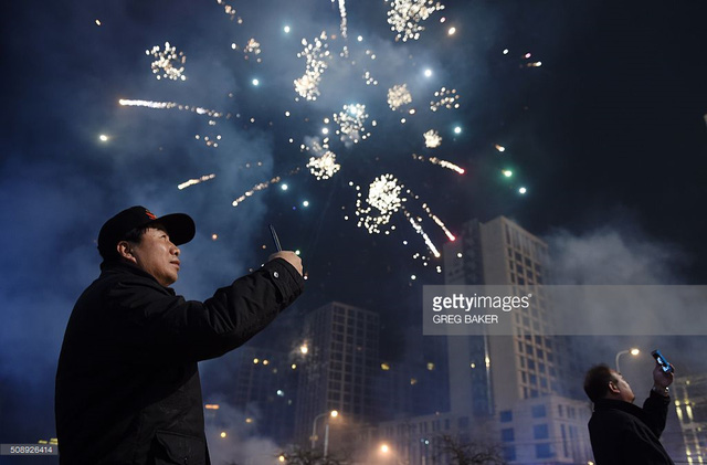Hai người đàn ông chụp ảnh pháo hoa tại thủ đô Bắc Kinh, Trung Quốc (Ảnh: Getty Images)
