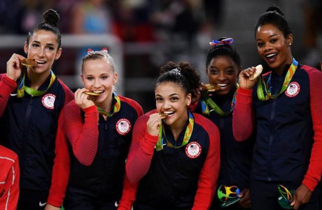 6/ Đội thể dục dụng cụ nữ Mỹ, gồm từ trái, Alexandra Raisman, Madison Kocian, Lauren Hernandez, Simone Biles và Gabrielle Douglas, tươi cười với huy chương vàng,