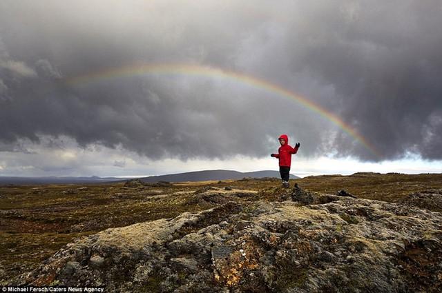 Dù mây đen cuồn cuộn u ám, nhưng sự xuất hiện của cậu bé áo đỏ bên dưới cầu vồng vẫn khiến bức ảnh đẹp ngỡ ngàng.