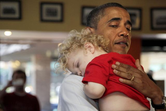 Một em bé đang dựa đầu trên vai Tổng thống Obama và ngủ ngon lành.