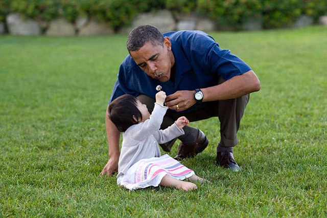 Tổng thống Obama cùng một em bé thổi những cánh hoa bồ công anh.