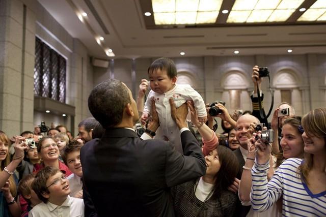 Tổng thống nhấc bổng một em bé lên cao trong một chuyến thăm tới Nhật Bản.