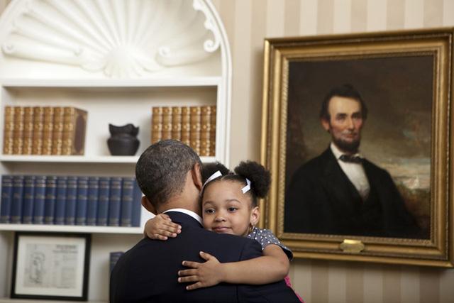 Cố Tổng thống Abraham Lincoln có vẻ rất hài lòng khi thấy Tổng thống Obama đang ôm một cô bé đáng yêu trong phòng Bầu Dục